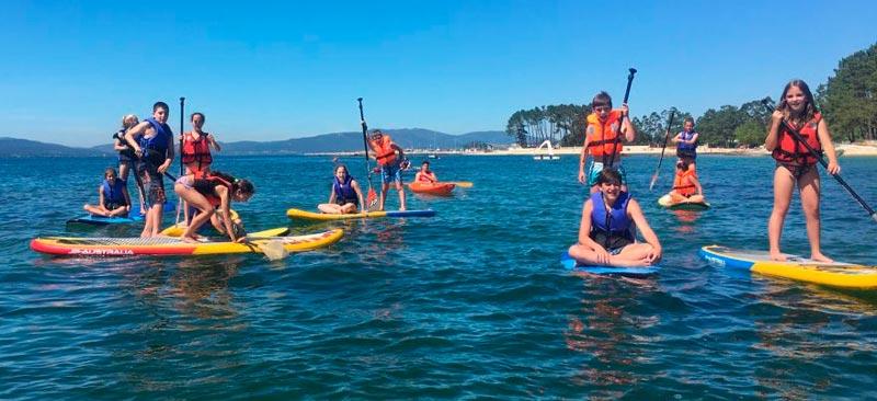 niños haciendo paddle surf en las rias baixas